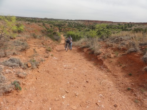 pushing the bike uphill at caprock canyon eagle trail