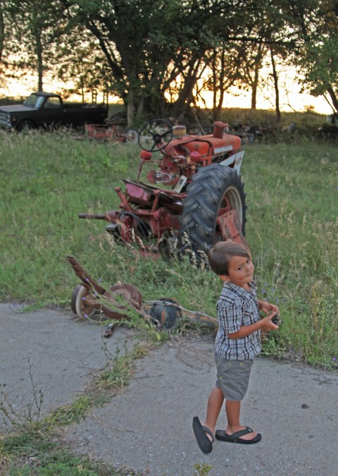 nebraska farm boy and old tractor in the sunset