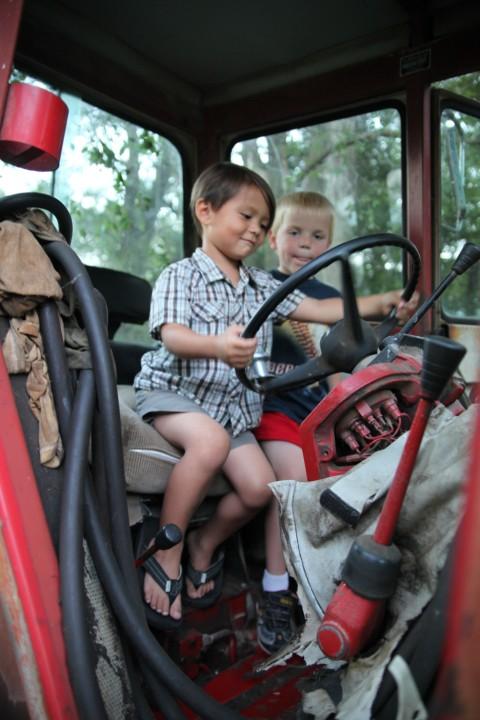 boys pretending from old nebraska farm tractor