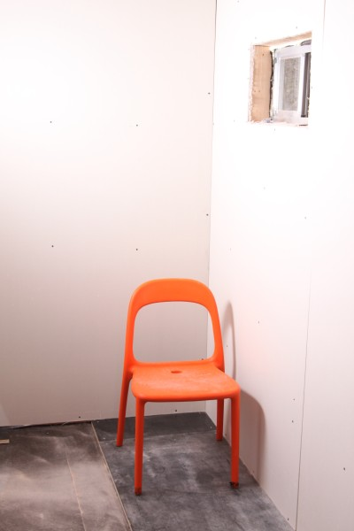 lonely orange chair meets drywall