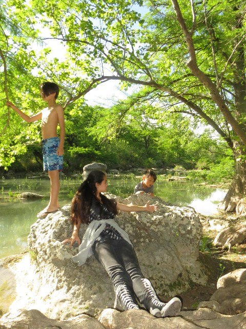 kids on a rock in the blanco river wimberley texas
